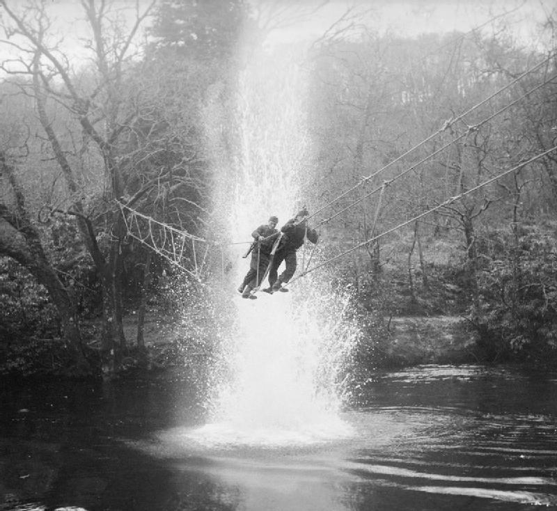 Commandos cross a river on a 'toggle bridge' under simulated artillery fire at the Commando training depot at Achnacarry, Inverness-shire, Scotland, January 9, 1943. H 26620. Part of War Office Second World War Official Collection. War Office official photographer Lockeyear WT (Lt)
